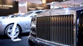 rolls royce : Rolls Royce Ghost front grille with the Spirit of Ecstasy on top at the motor show. The camera is sliding from right to left.