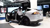 tesla motors : BRUSSELS, BELGIUM - JANUARY 13: Tesla Model X all-electric, luxury, crossover SUV car with two women stepping into the car during the 2017 European Motor Show Brussels.