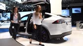 tesla motors : Tesla Model X all electric, luxury, crossover SUV car with two women stepping out of the car during the 2017 European Motor Show Brussels.