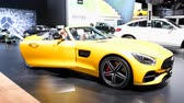 roadster : Mercedes-AMG GT Roadster luxury performance car on display at the 2018 European Motor Show Brussels. A man and woman are sitting inside the car.