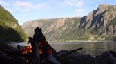 log : Campfire on the shore of a Fjord in Norway during summer vacation.
