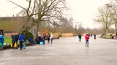 paten yapma : People ice skating on frozen canals in the Weerribben Wieden nature reserve in Holland during a beautiful cold winter day.