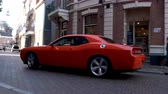 dodge : Dodge Challenger SRT American muscle car sports car driving in a street in the city of Zwolle during a sunny summer morning. People in the background are looking at the cars.
