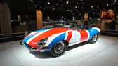 motor show : BRUSSELS, BELGIUM - JANUARY 8 ,2020: Jaguar E-Type Roadster classic sports car with a Uninon Jack flag painted on the body on display at Brussels Expo Stock Footage