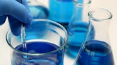 luva : This is a close up photo of a scientist stirring a blue liquid in a beaker. He is wearing blue rubber gloves and there are other beakers and glass bottles in the background that fall out of focus.