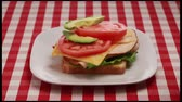 авокадо : This is a step by step video of a turkey sandwich being built on a red and white checkered picnic table cloth.It has a lot of fresh healthy ingredients such as tomatoes, pickles, lettuce, avocado and cheese.It has a lot of fresh healthy ingredients such a