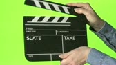produkcja : Woman slating a take with clapper board on green screen