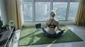 iç : Young girl practicing meditation at home with cityscape background outside the window. Keep calm. Practicing yoga in the morning. Breathing, relaxing exercises on sunrise. Healthy and sport lifestyle.