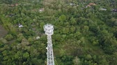передатчик : Aerial view of cell phone communication tower in green nature of city against blue sky. Scenic shot of world telecommunication concept. Стоковые видеозаписи