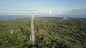 transfer station : Aerial view of cell phone communication tower in green nature of city against blue sky. Scenic shot of world telecommunication concept. Stock Footage