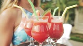 smoothies : Summer pool party. Close up of fresh juice. Girl with a tray and glasses with smoothie. Happy group of young friends enjoying the natural drinks together in the resort. Healthy lifestyle.