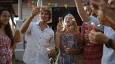 Happy group of people making a toast, having fun, smiling, enjoying picnic party with drinks outdoors together. Young friends celebrating birthday. Holiday celebration festive party. Teenage lifestyle