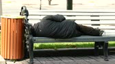 manmetro : Homeless tramp beggar man sleeps on city bench. Contrasts of e city .4K 3840x2160 Stock Footage
