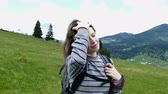 summer : Young girl tourist do up hair in mountain hills. Steady shot