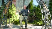 símbolo : Slow motion. Adult man rides a swing in summer day