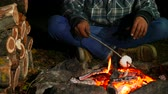 fogueira : man roasting marshmallows at camp fire