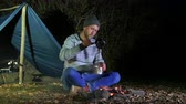 ash : 4k. Young man drink coffee or tea at camp fire. Life on travel, evening time Stock Footage