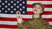 united states : Smiling young girl soldiers do sign victory in front of US flag