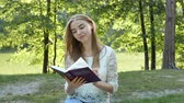 sólido : 4k. Attractive smiloing Girl reads Bible in park. Christian team shot