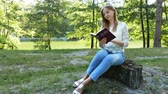 sólido : 4k.Young modern girl reads Bible in summer park. Christian beliefs