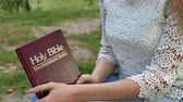 sólido : 4k. Body of Girl sit outdoor with Bible. Study Christianity, dolly shot