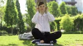 myśl : Young woman using headphones, and working in the park. Wideo