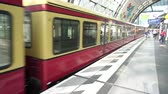 pendulares : Berlin Hauptbahnhof, Germany, April 14 2018: S-Bahn train departing from Deutsche Bahn DB Main Railway Station platform, red wagons with commuters gaining speed, Berlin Central Station indoor view