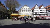 half timbered : Soest, Germany, April 18 2018: City center of Soest, central street, square, open air cafe, local people, traditional german half-timbered house fachwerkhaus with timber frame, man riding bicycle, 4K.