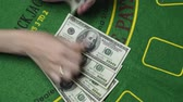 дилер : Blackjack dealer female hands count money. Hundreds US Dollar bills or notes in cash on Blackjack green deck table in casino. Background concept of gambling game and entertainment in Vegas, close up