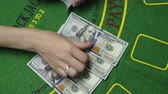 poker : Female dealer hands counting money. Hundreds US Dollar bills or notes in cash on Blackjack green deck table in casino. Background concept of gambling game and entertainment in Vegas, close up