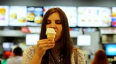 Young woman eating ice cream on the food court