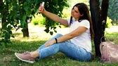 Young sitting on the grass and making selfie with a mobile phone Stockvideo