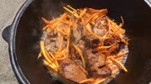 pilau : Cooking of pilaf outdoor. Chopped lamb frying in cauldron.