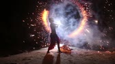 Artist turns the fireworks around itself on the background of rocks in fire performance Stok Video