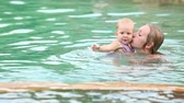 bebekler : Daughter holds the ball and swims next to his mother in the pool