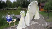party : white arch for wedding on the lake near the trees and stone paths and wooden houses