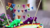 backlit : creamy cake decorated with toy cars and inscription Happy Birthday