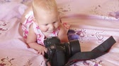 young : child in pink dress lay on the bed and play with black camera Stock Footage