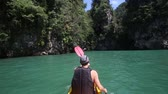 caiaque : elderly man rowing a kayak across the azure sky-blue sea and swims in the canyon
