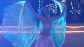 clothe : young blonde girl  in theatrical costume with wings turns round and dances belly dance at the wedding party