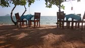 camera moves between two restaurant tables with waving clothes served at sand beach against sea and boats Stok Video