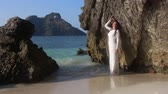 inclinar : brunette bride in white wedding dress stands in transparent  shallow water and  leans on large cliff against islands