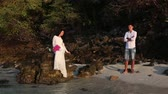 длинношерстный : brunette bride sits on rock in sea and handsome groom looks at her from beach against rocky islands at sunrise