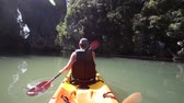 people : european man backside view in life-vest rows on kayak to river mouth in canyon and splashes