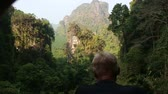 kamie�� : european man backside view looks at canyon cliffs in Thailand jungle