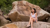 wild : Vietnamese girl closeup sits on large brown rock and admires scenery of stones hills plants and mountain stream Stock Footage