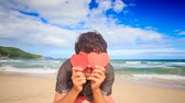 romance : closeup European guy hides face behind hand-made red hearts smiles on beach against wave surf of azure sea