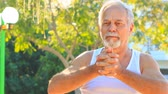 manmetro : closeup european bearded old man in white vest does morning exercises stretches hands fingers in park