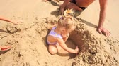 humor : camera removes from grandpa little blond girl boy squat play with toys in hole among sand heap on beach