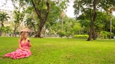 city : young blond girl in long red pink dress sits on grass drinks juice with straw in tropical park near resort city street